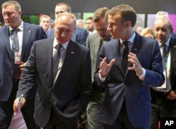 Russian President Vladimir Putin, left, listens as France's President Emmanuel Macron speaks to him at the G-20 summit in Buenos Aires, Nov. 30, 2018.