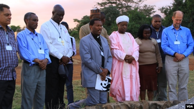 Representatives of the Christian, Muslim, Hindu, and Buddhist faiths pray for Africa's wildlife at the historic Ivory Burning Site in Nairobi National Park, Kenya, September 20, 2012. (J. Craig/VOA)