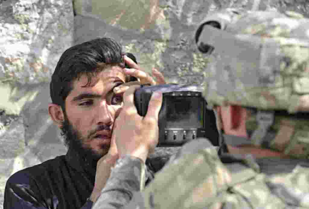 Un soldado estadounidense registra los ojos de un residente afgano con un sistema de identificación biométrico automatizado, ABIS, durante una misión en Turkham.