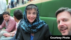 Barbara Slavin, wearing the required headscarf, and Thomas Erebrink of the New York Times, await Hassan Roouhani's swearing-in in Iranian parliament August 4.