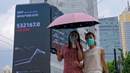 Dua pejalan kaki mengenakan masker, berjalan di dekat papan iklan elektronik yang menunjukkan indeks Produk Domestik Bruto (PDB) China di gedung perkantoran komersial di Shanghai, China, 24 Agustus 2021. (AP Photo/Andy Wong, File)