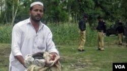 Seorang warga Pakistan memungut pakaian korban bom bunuh diri di Khyber Pakhtunkwa (15/9).