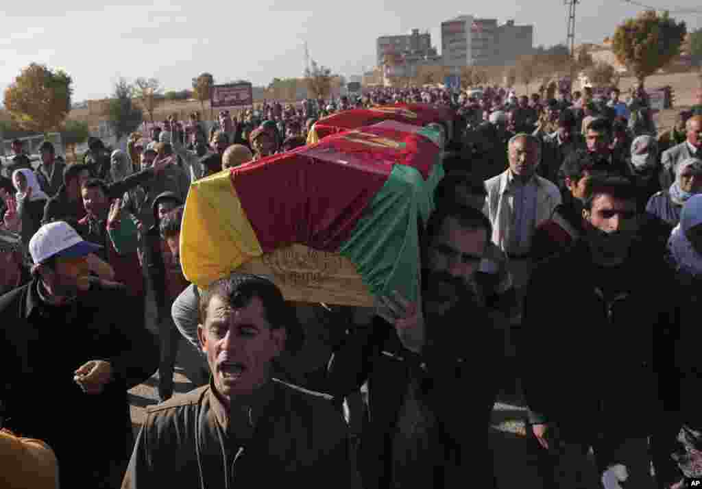 Mourners carry the coffin of a Kurdish fighter, killed while fighting Islamic State militants in Kobani, Syria, Oct. 23, 2014.
