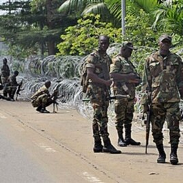 Armed members of the New Forces adopt combat positions near the hotel that houses the rival government declared by Alassane Ouattara in Abidjan, Ivory Coast, 13 Dec 2010