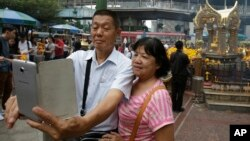 """FILE - Asian tourists takes a """"selfie"""" in front of the Erawan Shrine in Bangkok, Thailand, Oct. 22, 2015."""