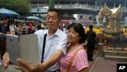 Turis mengambil swafoto atau 'selfie' di kuil Erawan di Bangkok, Thailand. (Foto: Dok)