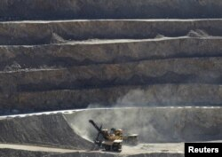 FILE - A mechanical shovel scoops up rocks to be loaded onto waiting dump trucks during a normal work day at the Chuquicamata open pit copper mine in northern Chile, April 1, 2011.