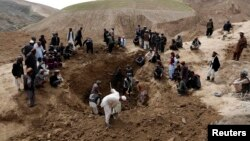 Afghan villagers gather at the site of a landslide at the Argo district in Badakhshan province, May 4, 2014.