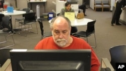 FILE - Richard Mattos, 59, looks for jobs at state-run employment center in Salem, Oregon.