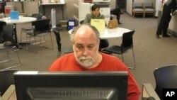 FILE - Richard Mattos, 59, looks for jobs at state-run employment center in Salem, Oregon.