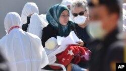Seorang migran perempuan yang menggendong bayinya menerima bantuan darurat setelah berhasil diselamatkan dari kapal yang tenggelam, di pelabuhan Messina, Sisilia, Italia (18/4).