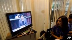 Seorang reporter sedang mengamati siaran televisi yang menayangkan jalannya sidang di Mahkamah Konstitusional Thailand, saat PM Yingluck Shinawatra menyampaikan pembelaannya, Selasa (6/5).