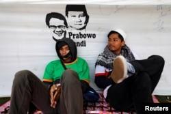 Dua pemuda beristirahat di sela kampanye pasangan capres-cawapres Prabowo Subianto di Solo,10 April 2019.