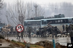 FILE - Indian paramilitary soldiers stand by the wreckage of a bus after an explosion in Pampore, Indian-controlled Kashmir, Feb. 14, 2019.