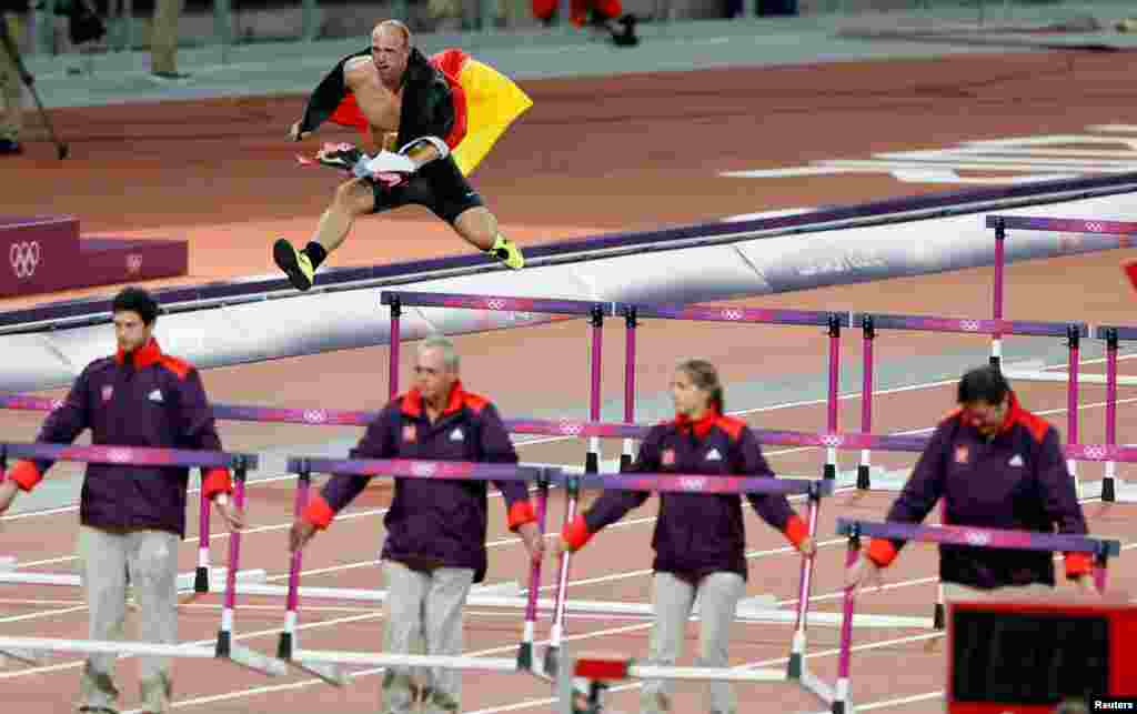 Germany's Robert Harting celebrates winning the men's discus throw final by grabbing a German flag, running a lap of the track over the hurdles, and trying to wrench one of the burning torches from the Olympic cauldron.