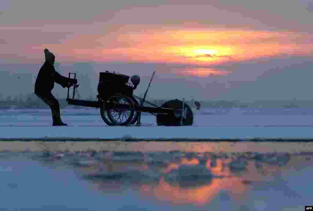 Seorang pria memotong balok-balok es dari sungaiSonghua di Harbin, China yang bekuuntuk dipakai dalam festival es yang akan dibuka awal bulan depan.