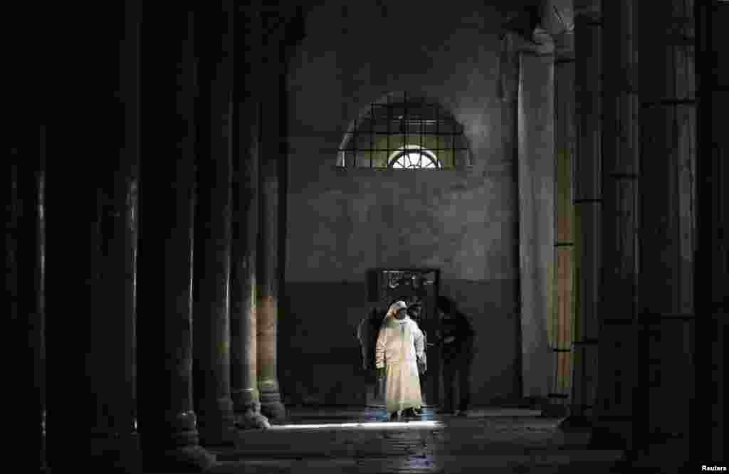 A nun walks inside the Church of the Nativity ahead of Christmas in the West Bank town of Bethlehem, Dec. 23, 2013.