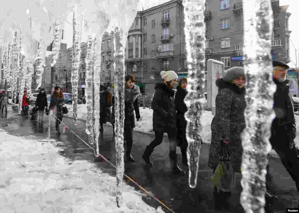 People walk past icicles, which hang from the roof of a building in a street in central Kyiv, Ukraine.