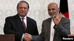 Afghan President Ashraf Ghani (R) shakes hands with Pakistani Prime Minister Nawaz Sharif after a news conference in Kabul, May 12, 2015.