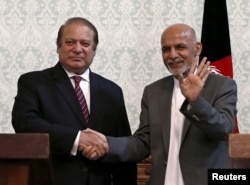 FILE - Afghan President Ashraf Ghani (R) shakes hands with Pakistani Prime Minister Nawaz Sharif after a news conference in Kabul.