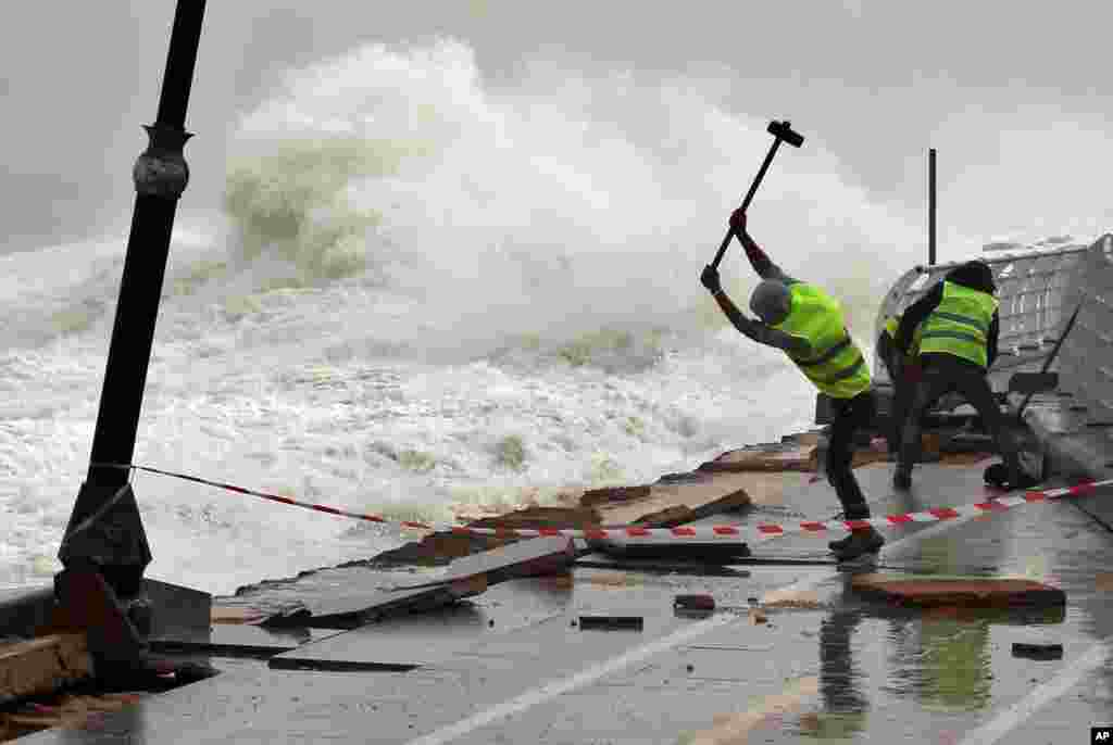 Workers remove broken tiles near the fence of Beirut's seaside corniche, which was damaged by strong waves in Lebanon.