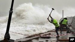 Pekerja memperbaiki pagar pembatas di pinggir pantai yang rusak dihantam ombak di Beirut, Lebanon.