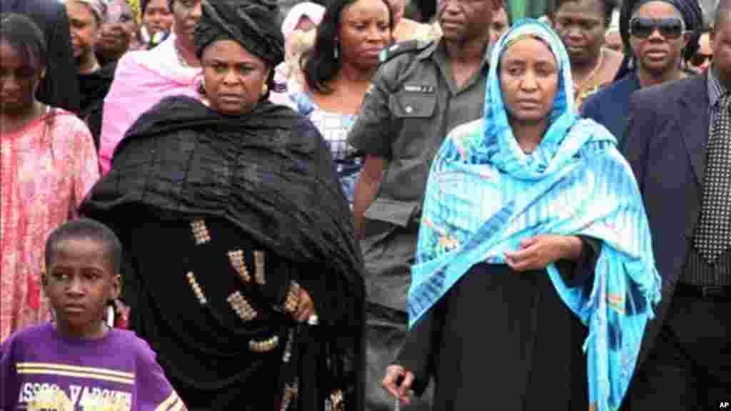 Turai Yar'Adua, wife of late President Umaru Yar'Adua, stands with Patience Jonathan as her husband's body is loaded into a plane to be transported for burial in Katsina, May 2010.