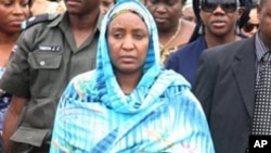 Turai Yar'Adua, wife of late President Umaru Yar'Adua, stands with Patience Jonathan as her husband's body is loaded into a plane to be transported for burial in Katsina.