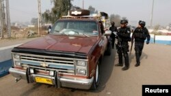 Seorang polisi tengah memeriksa identitas pengemudi di sebuah pos pemeriksaan di distrik Abu Ghraib sebelah barat kota Baghdad (9/1), meyusul serangan bom yang menewaskan 21 orang dan melukai 25 lainnya di sebuah pusat perekrutan anggota militer di wilayah itu.