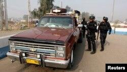 9일 이라크 바그다드에서 폭탄테러가 발생한 가운데 경찰이 검문소를 통과하는 운전자의 신원을 확인하고 있다.