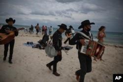 """Musisi keliling """"Los Compas"""" mencari turis untuk mengamen di pantai Mamitas, di Playa del Carmen, negara bagian Quintana Roo, Meksiko, Selasa, 5 Januari 2021."""