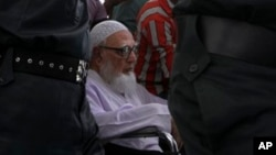 Ghulam Azam, mantan pemimpin Jamaat-e-Islami, partai Islam Bangladesh, dikawal ketat petugas keamanan menuju ruang sidang Mahkamah Kejahatan Perang di Dhaka, Bangladesh (15/7).