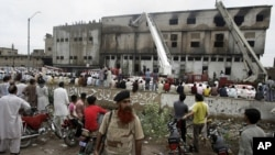 People gather at the site of burnt garment factory in Karachi, Pakistan, September 12, 2012.