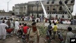 九月十二号人们聚集在卡拉奇不 被烧毁的服装厂外