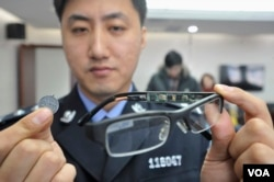 A police officer displays a pair of glasses with a hidden camera and a tiny receiver attached to a coin, which are both exam cheating equipment confiscated by the police, in Shenyang, Liaoning province in 2013. (REUTERS)