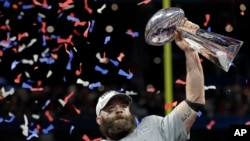 Pemain tim New England Patriots, Julian Edelman, mengangkat piala setelah timnya menjuaarai NFL Superbowl ke-53 melawan Los Angeles Rams, Minggu, 3 Februari 2019 dengan skor 13-3 (foto: AP Photo/David J. Phillip)