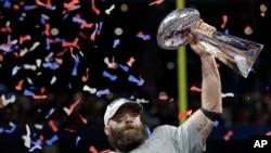 Pemain tim New England Patriots, Julian Edelman, mengangkat piala setelah timnya menjuaarai NFL Superbowl ke-53 melawan Los Angeles Rams, Minggu, 3 Februari 2019 dengan skor 13-3 (foto: AP Photo/David J. Phillip)
