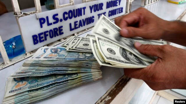 A worker counts U.S. dollar bills and Philippine pesos inside a money changer in Manila, June 19, 2013.