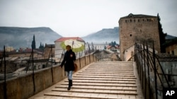 FILE - A woman crosses the old bridge in Mostar, in Bosnia and Herzegovina, Jan. 20, 2013.