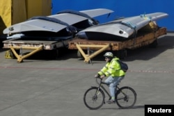FILE - A worker leaves the Boeing Everett Factory on a bicycle, amid the coronavirus disease (COVID-19) outbreak, in Everett, Washington, U.S. March 23, 2020. (REUTERS/David Ryder)