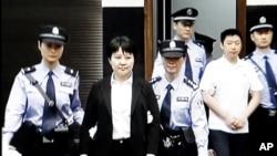 中央电视台画面显示薄熙来妻子谷开来(中间站立者)2012年8月9日在中国东部的合肥市中级人民法院出庭受审(2012年8月9日)