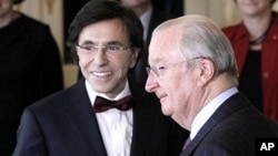 The chief of Belgium's francophone Socialist Party (PS) Elio Di Rupo (L) poses with King Albert II (R) after being sworn in as Prime Minister at the Laeken Royal Palace in Brussels December 6, 2011.