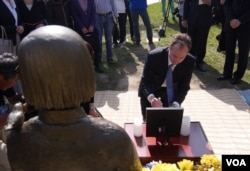谢安达在慰安妇铜像和照片前拈香(美国之音记者国符拍摄)
