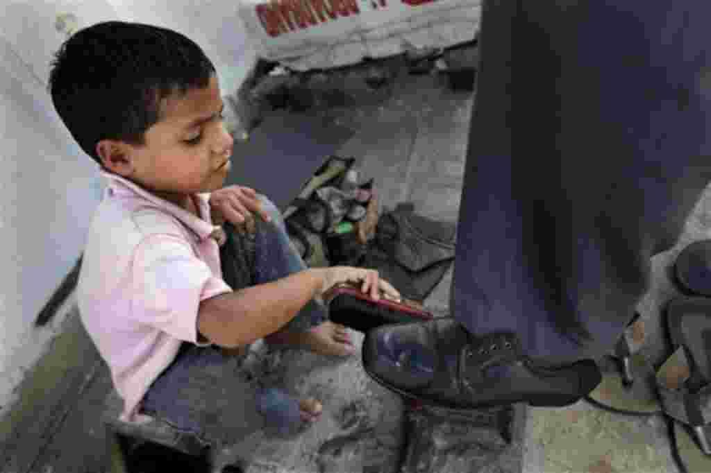 Kapil Kumar, de 6 años, limpia botas en una tienda improvisada en una acera de Gauhati, India.