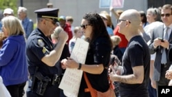 A police officer confronts a woman holding a sign at the North Carolina State Capitol in Raleigh, North Carolina, April 11, 2016.