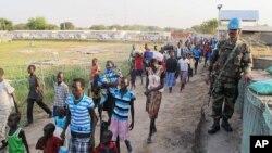 Seorang tentara pasukan perdamaian PBB berjaga-jaga saat barisan penduduk sipil tiba di kompleks badan PBB UNMISS di Juba untuk mengungsi (17/12). (AP/Rolla Hinedi)