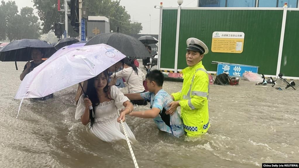河南省郑州市一名交通警察用一条绳子帮助居民过洪水湍急的街道。 (2021年7月20日)(photo:VOA)