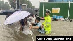 河南省鄭州市一名交通警察用一條繩子幫助居民過洪水湍急的街道。 (2021年7月20日)