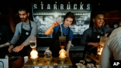 "FILE - Starbucks employees prepare coffee in the lobby of the company's annual shareholders meeting in Seattle, Washington. That boss-to-worker pay ratio is slightly lower than it has been in the past few years, but is still ""light years"" higher than the 20-to-1 gap between workers and bosses in 1965, or the 59-to-1 difference that was measured in 1989."
