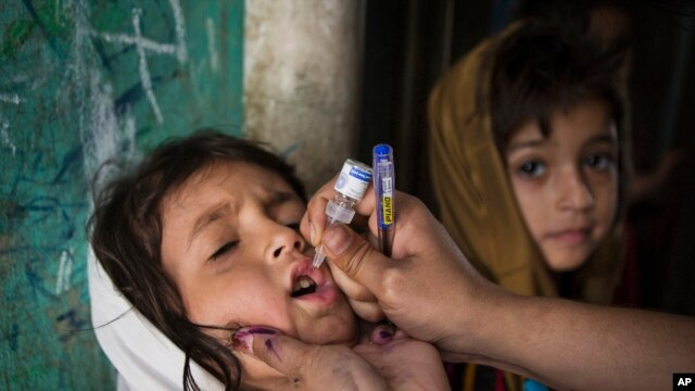 A Pakistani health worker gives a child a polio vaccine in Rawalpindi, Pakistan, Tuesday, April 8, 2014